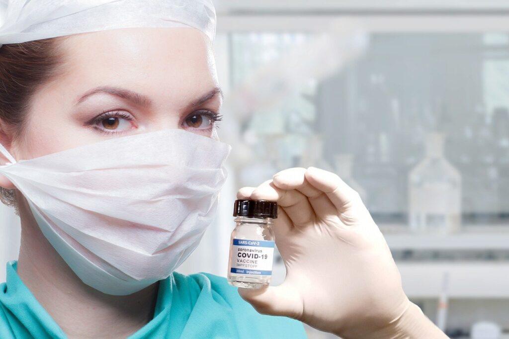 Frau mit Impfstofffläschchen